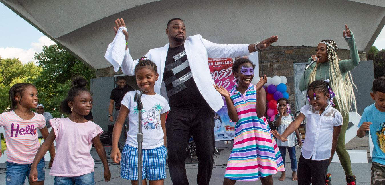 Representative Kirkland dancing with group of children at summer outdoor event