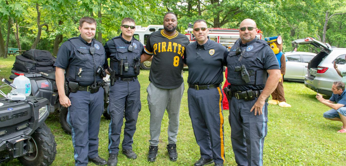 Representative Kirkland wearing Pittsburgh Pirates jersey and posing for photo with police officers