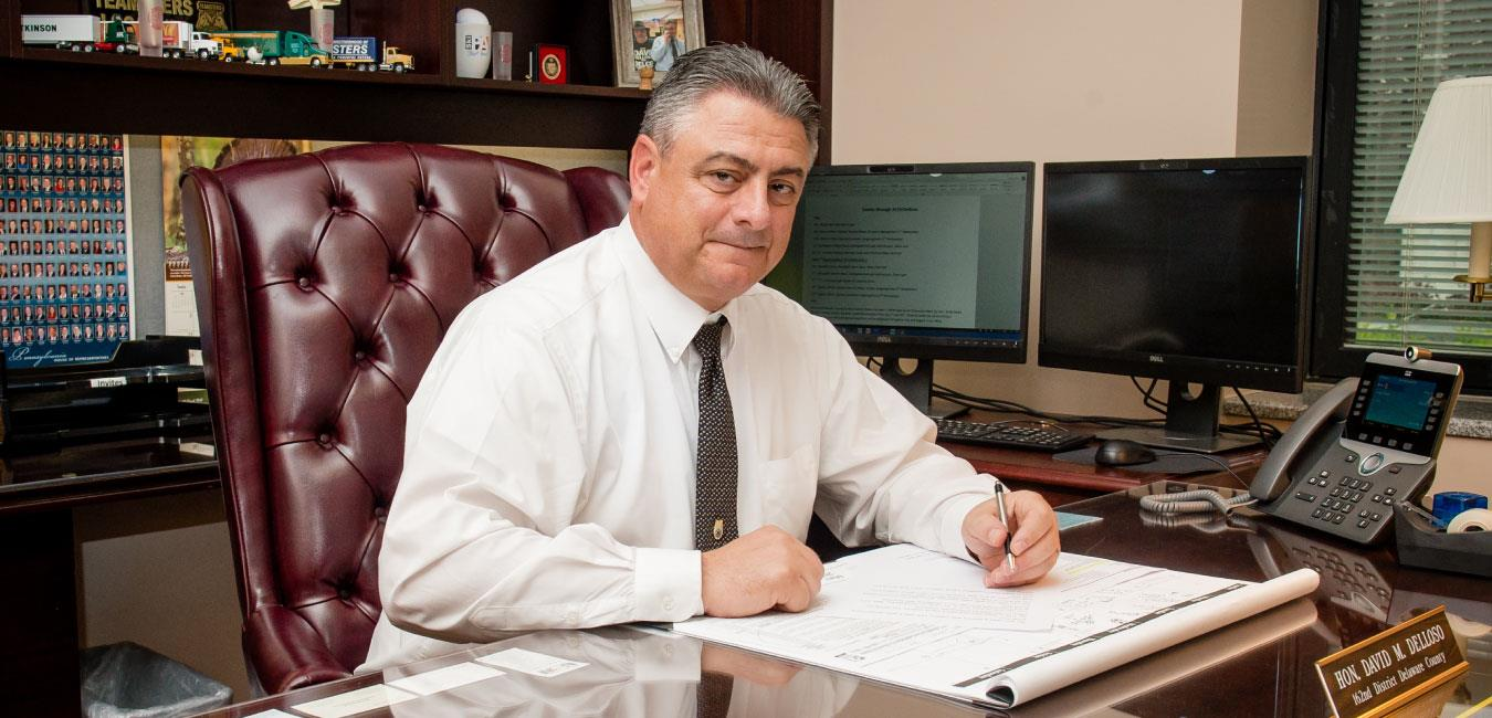 Representative Delloso sitting at desk posing for photo