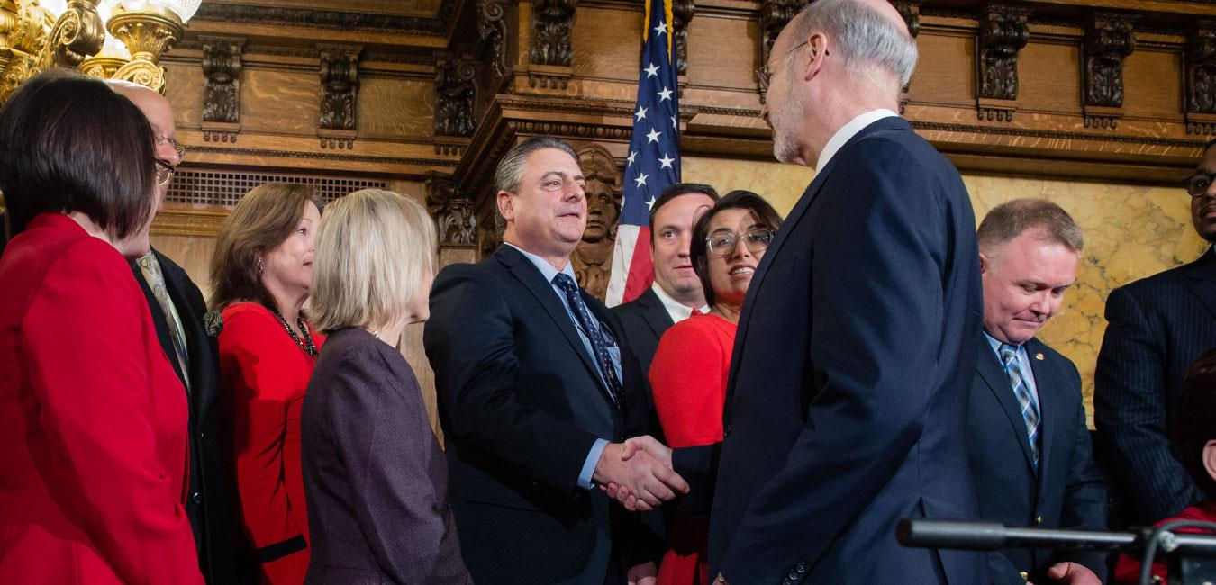 Representative Delloso standing next to fellow legislators in Governor's Reception Room and shaking hands with Governor Wolf