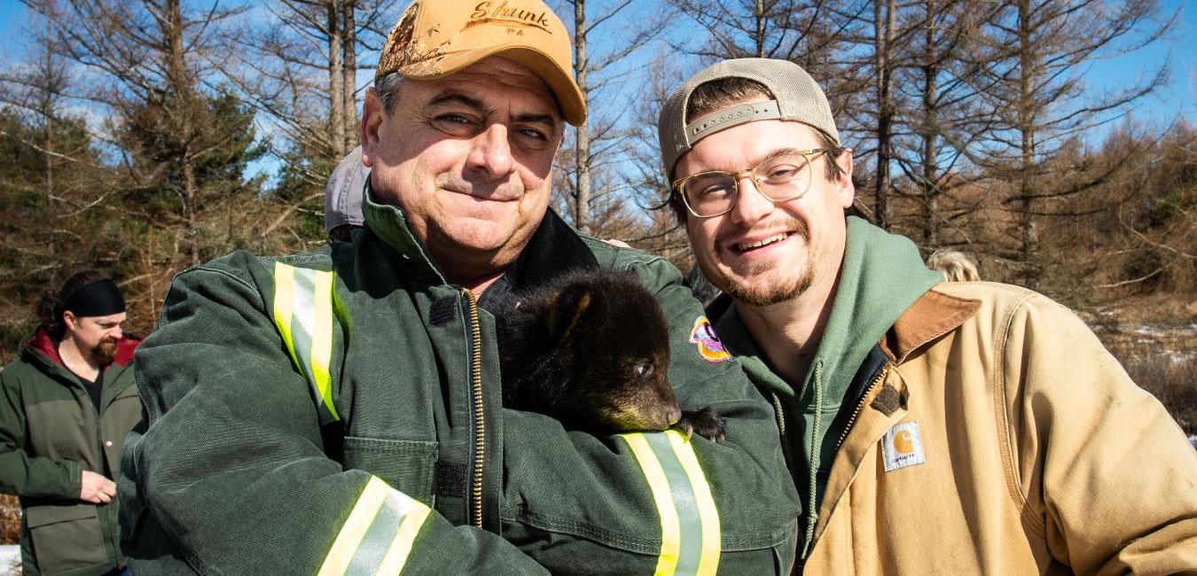 Representative Delloso holding baby bear in green jacket and posing for photo with man