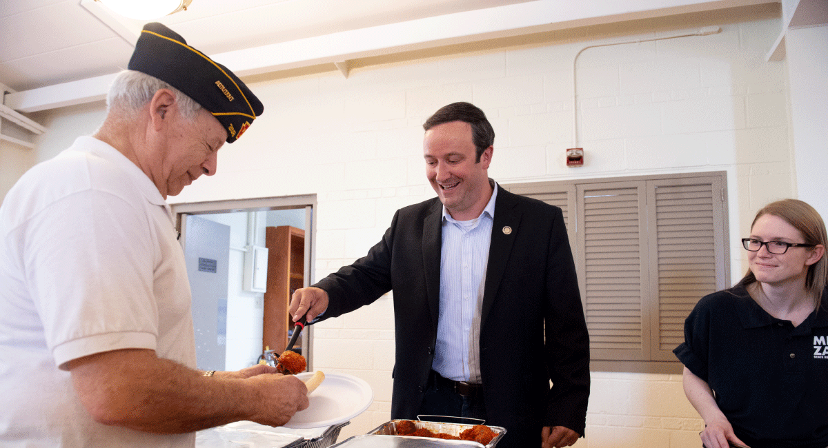 Representative Zabel smiling and serving food to elderly veteran