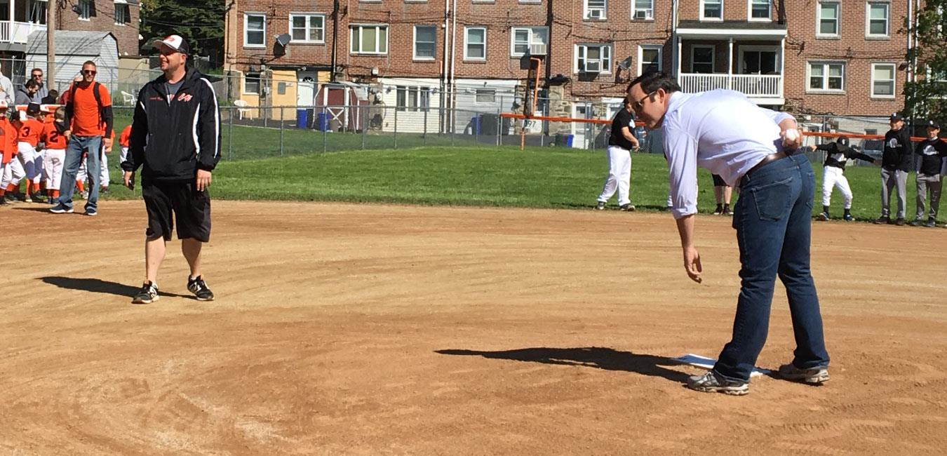 Representative Zabel winding up to throw first pitch at baseball game