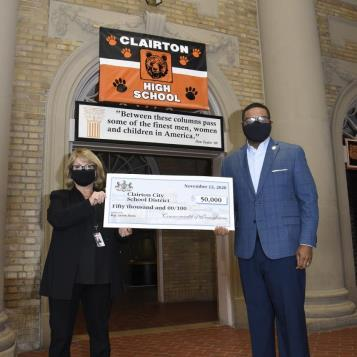 Rep. Austin Davis presents Clairton School District superintendent Dr. Ginny Hunt a check for $50,000 for a PDE grant to address structural damage to school buildings.