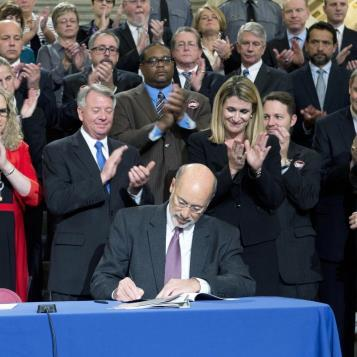 Gov. Tom Wolf is congratulated by lawmakers and advocates as he signs a package of bills into law to give the state more tools in the ongoing fight against heroin and opioid abuse.