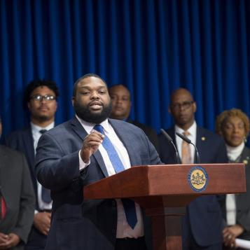 Democratic whip Jordan Harris is joined by his colleagues at a press event speaking on a package of bills aimed at streamlining police procedures and restoring confidence and impartiality in the investigation process.