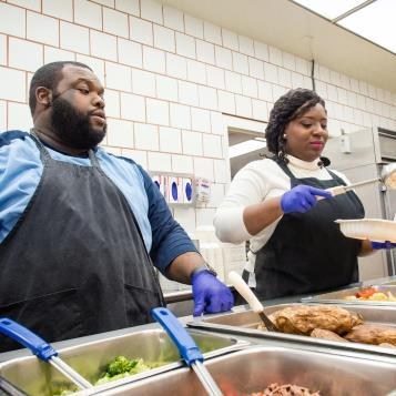 Democratic whip Jordan Harris and Democratic Caucus Chairwoman Joanna McClinton work behind the counter in the Capitol Cafeteria to raise awareness about the need to raise the minimum wage in Pennsylvania.