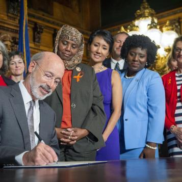 Reps. Movita Johnson Harrell, Patty Kim, Joanna McClinton, and Maureen Madden watch Governor Tom Wolf sign an executive order making unprecedented sweeping changes to executive branch agencies and programs to better target the public health crisis of gun violence in Pennsylvania.