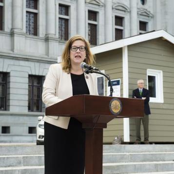 "Representative Krueger-Braneky speaks at a Harrisburg ""Unfreeze PA's Energy Codes"" news conference to discuss current energy conservation codes compared to above-code buildings.  To demonstrate the differences, two ""icehouse"" buildings were constructed, with a huge block of ice set inside the structure to determine the rate of ice melt within a standard energy conservation code building, and one constructed to above-code standards."