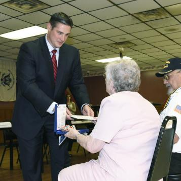 Rep. Brandon Neuman presents a Korean Ambassador for Peace Medal to a veteran of the Korean War in appreciation of their service and sacrifice.